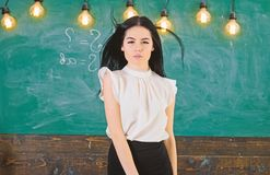 Teacher ready to start lesson, copy space. Woman with long hair in white blouse stands in classroom. Lady teacher on. Pensive face stands in front of chalkboard royalty free stock photography