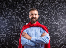 Teacher in red cape against big blackboard with mathematical symbols. Hipster teacher in red cape standing against big blackboard with mathematical symbols and royalty free stock images