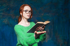 Teacher with red hair in glasses reading book and gesticulates Stock Photography