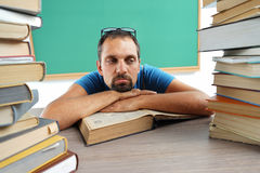 Teacher resting his chin on his hands, laying on a table with opened book Royalty Free Stock Photo