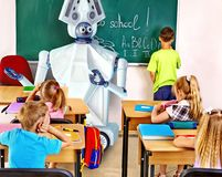 Teacher robot with school children in school class near blackboard. Royalty Free Stock Photos