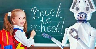Teacher robot with schoolchild girl in school class near blackboard. Teacher robot with schoolchild girl in school class next to blackboard. Interactive ai Stock Photo