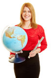 Teacher with a rotating globe as a geography lecturer. Smiling blond teacher with a rotating globe as a geography lecturer stock image
