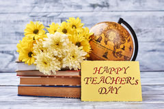Teacher`s Day card and flowers. Globe and stack of books. Appreciate your teacher Stock Photos