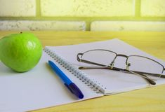 Teacher's Day concept and back to school, green Apple, book, laptop, reading glasses and pen on wooden table, sunlight. Business design books office paper royalty free stock images