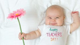 Teacher`s Day message with baby girl. Holding a flower Stock Photography