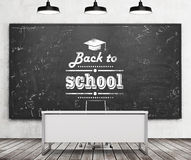 Teacher's desk in a modern university or school. A huge black chalkboard on the wall with written down phrase - Back to school. Stock Photo