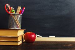 Teacher`s desk with writing materials, a book and an apple, a blank for text or a background for a school theme. Copy space.  stock images