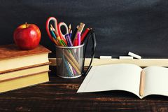 Teacher`s desk with writing materials, a book and an apple, a blank for text or a background for a school theme. Copy space.  royalty free stock image