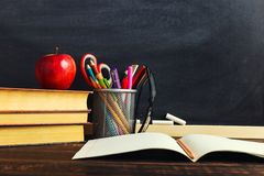 Teacher`s desk with writing materials, a book and an apple, a blank for text or a background for a school theme. Copy space.  stock photography
