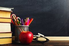 Teacher`s desk with writing materials, a book and an apple, a blank for text or a background for a school theme. Copy space.  royalty free stock photography