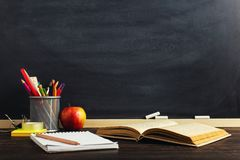 Teacher`s desk with writing materials, a book and an apple, a blank for text or a background for a school theme. Copy space.  royalty free stock photo