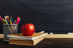 Teacher`s desk with writing materials, a book and an apple, a blank for text or a background for a school theme. Copy space.  royalty free stock images