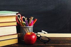 Teacher`s desk with writing materials, a book and an apple, a blank for text or a background for a school theme. Copy space.  royalty free stock photos