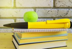 Teacher&-x27; s dnia poj?cie i z powrotem szko?a, zielony Apple, wielki pami?tkarski pi?ro na ksi??kach i notatnikach, ?wiat?o s? obraz royalty free