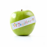 Teacher's Green Apple. Green apple isolated against white background with colorful teacher label. Copy space Stock Photos