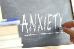 Hand writing on a chalk board the word Anxiety in a mental health class. Psychology disorder concept. Teacher`s hand writing on a chalk board the word Anxiety stock image