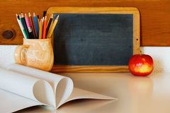 Teacher`s or knowledge day concept with a blackboard and a heart of textbook pages Stock Images