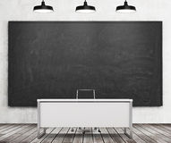 Teacher's or professor's desk in a modern university. A huge black chalkboard on the wall and three black ceiling lights, wooden f Royalty Free Stock Photography