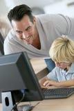 Teacher with school boy on desktop computer Stock Photo