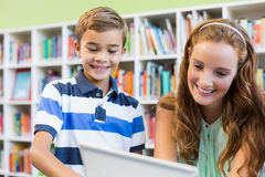 Teacher and school boy using laptop in library Stock Images