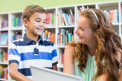 Teacher and school boy using laptop in library Royalty Free Stock Photos