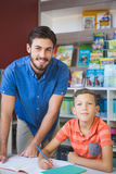 Teacher and school kid smiling in library Stock Images
