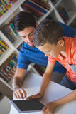 Teacher and school kid using digital table in library Royalty Free Stock Photo