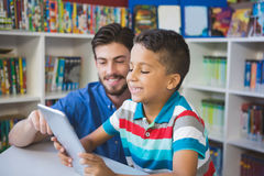 Teacher and school kid using digital table in library Royalty Free Stock Photography