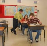 Teacher School Lessons. Three students in classroom, teacher helping teen girl Royalty Free Stock Image