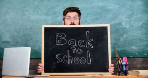 Teacher or school principal welcomes inscription back to school. School life full of stress. Educator hiding behind. Blackboard. Man scared beginning school stock image
