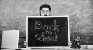 Teacher or school principal welcomes inscription back to school. School life full of stress. Educator hiding behind. Blackboard. Man scared beginning school royalty free stock images