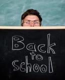 Teacher or school principal welcomes inscription back to school. Teachers life full of stress. Teacher peeking out of. Blackboard. Man scared beginning school stock images