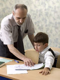 Teacher and schoolboy. The teacher checks a homework of the pupil Stock Images