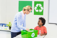 Teacher and schoolboy discussing about recycle logo. In classroom Royalty Free Stock Photography