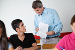 Teacher And Schoolboy Looking At Paper During. Happy male teacher and teenage schoolboy looking at paper during examination in classroom Royalty Free Stock Image