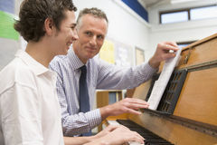 Teacher with schoolboy playing piano royalty free stock photo