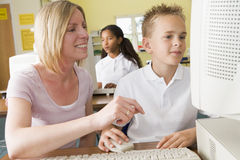 Teacher and schoolboy studying on a computer Royalty Free Stock Image