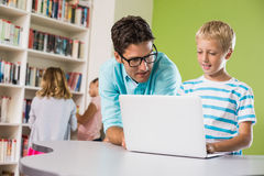 Teacher and schoolboy using laptop in library Royalty Free Stock Image