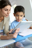 Teacher and schoolboy using tablet in class Royalty Free Stock Photography