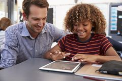 Teacher and schoolboy using tablet computer in class Stock Image