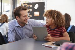 Teacher and schoolboy using tablet looking at each other Royalty Free Stock Images