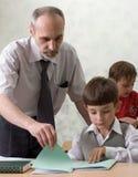 Teacher and schoolboys. The teacher checks a homework of the pupil Stock Photos