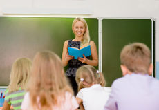Teacher and schoolchildren in classroom at lesson.  Stock Photography