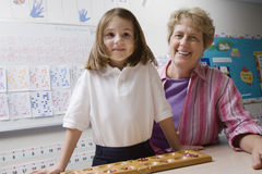 Teacher And Schoolgirl With Counting Tray Royalty Free Stock Photos