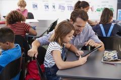 Teacher and schoolgirl using tablet computer in class Stock Photos