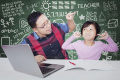 Teacher scolding his student in the class. Young teacher advising his female student to study in the classroom with a book and laptop Stock Photography