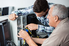 Teacher And Senior Man Fixing Computer In Class Royalty Free Stock Photography