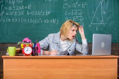 Teacher shocked face keep working after classes. Teacher woman sit table classroom chalkboard background. Work far. Beyond actual school day. Still working stock images