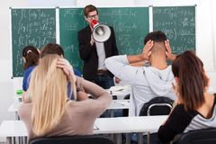 Teacher Shouting Through Megaphone On Students. Young teacher shouting through megaphone on university students in classroom Royalty Free Stock Image